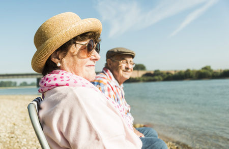 Germany, Ludwigshafen, senior couple sitting on folding chairs at riverside LANG_EVOIMAGES