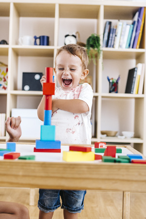 cries: Portrait of excited little boy playing with building bricks