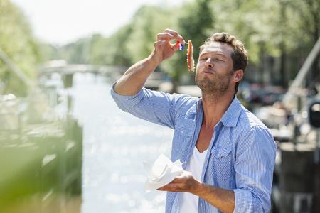 traditionally dutch: Netherlands, Amsterdam, man eating matjes herring