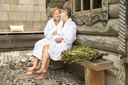 Lächelnde ältere Paare in den Bademäntel, die außerhalb des finnischen Saunablockhauses sitzen