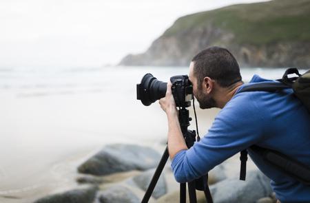Spain, Valdovino, photographer on the beach with tripod and camera