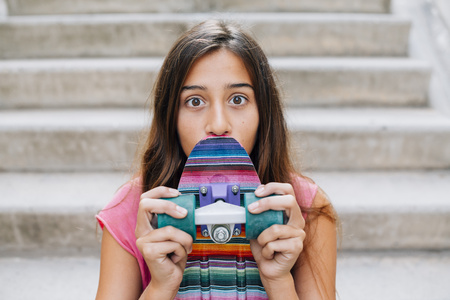 Portrait of wide-eyed teenage girl with a colorful skateboard sitting on stairs LANG_EVOIMAGES
