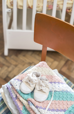 Stack of blankets and baby shoes on a chair