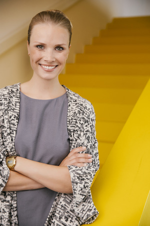 Portrait of smiling young woman with crossed arms standing in front of yellow stairs LANG_EVOIMAGES
