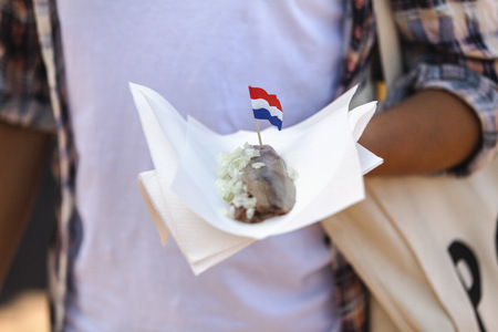traditionally dutch: Woman holding napking with matjes herring and Dutch flag LANG_EVOIMAGES