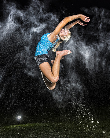 feet naked: Young woman jumping in the air in between cloud of flour