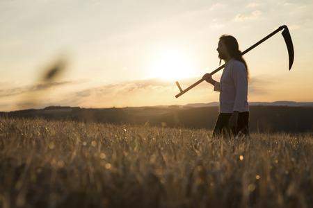 Organic farmer with scythe in barley field at sunrise