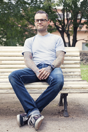Tattooed man sitting on a park bench