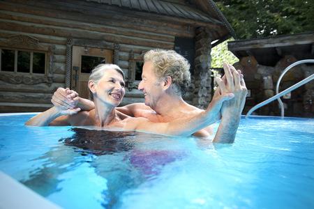 finnish bath: Happy senior couple in swimming pool at a spa
