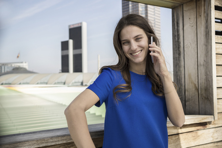 Germany, Frankfurt, smiling businesswoman telephoning with smartphone