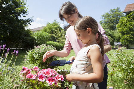 caucasian appearance: Smiling mother and daughter in garden planting flowers LANG_EVOIMAGES