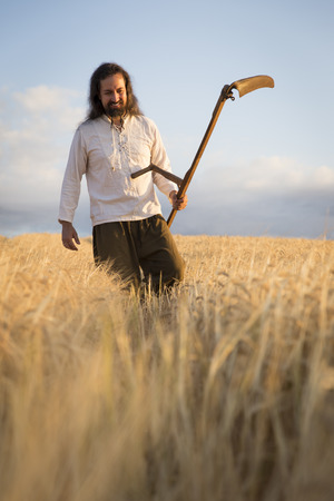 one mature man only: Organic farmer with scythe in barley field LANG_EVOIMAGES