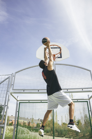 Young man playing basketball, dunking ball