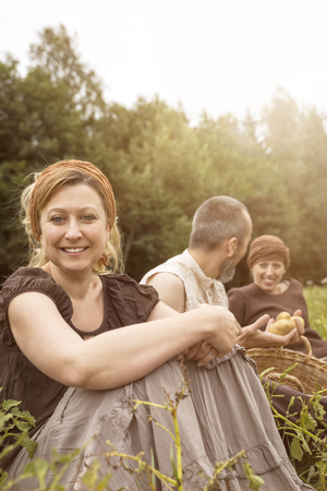 Smiling woman and two other people sitting on potato field LANG_EVOIMAGES
