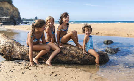 Spain, Colunga, four girls sitting on dead wood on the beach