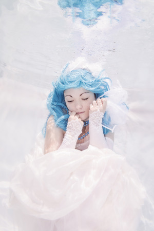 Young woman underwater, wedding dress and blue hair