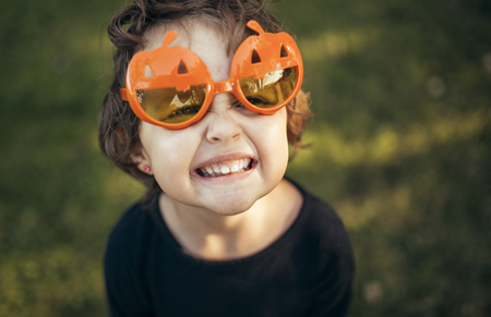 Portrait of little girl wearing halloween glasses shaped like pumpkins pouting mouth