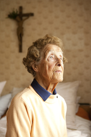 Portrait of aged woman sitting on bed in her bedroom