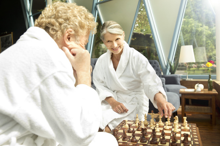 Senior couple in bathrobes playing chess