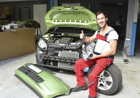 Car mechanic examining accident damaged car before repair
