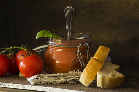 Fresh tomato soup with basil in preserving jar, tomatoes, white bread on wood