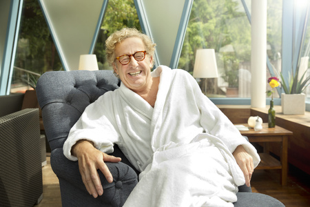 common room: Laughing senior man in bathrobe sitting in armchair LANG_EVOIMAGES