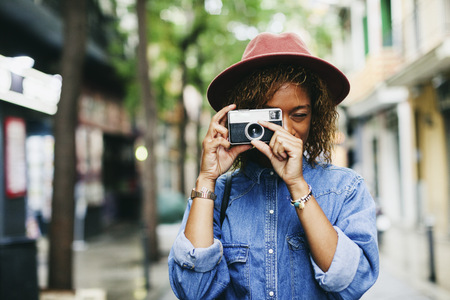 afroamerican: Spain, Barcelona, portrait of smiling young woman wearing hat and denim shirt taking picture with camera