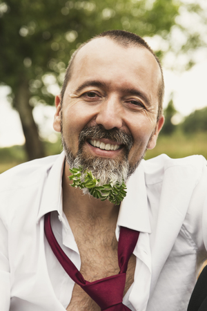 Portrait of smiling businessman with plant in his beard