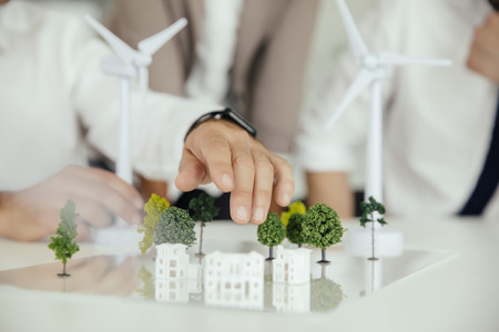 working attire: Close-up of business people wind turbine model and houses on conference table