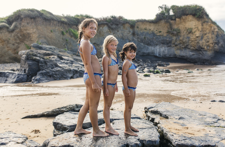 Spain, Colunga, three girls standing in a row on the beach