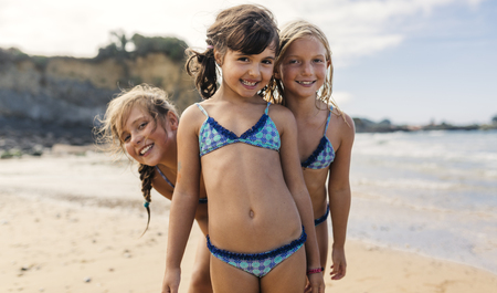 Spain, Colunga, three happy girls on the beach LANG_EVOIMAGES
