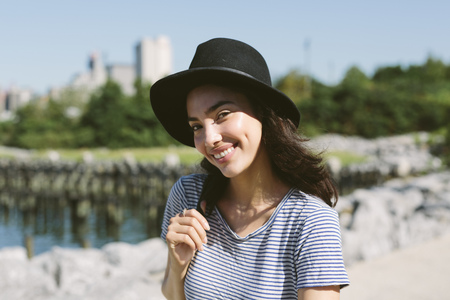USA, New York City, portrait of smiling young woman wearing black hat
