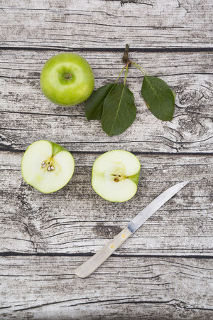 Sliced and whole Granny Smith, leaves and kitchen knife on wood