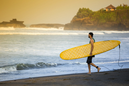 Indonesia, Bali, surfer walking on the beach