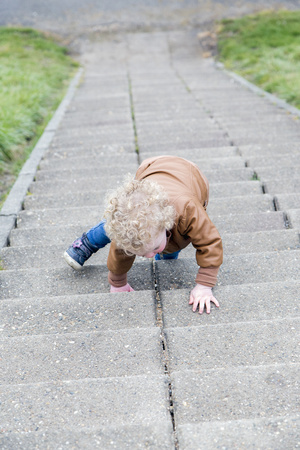 Little girl crawling up stairs