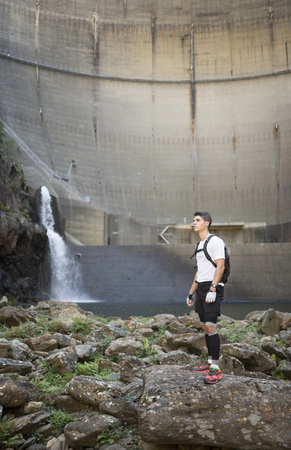 Ultra trail runner with a dam in the background LANG_EVOIMAGES