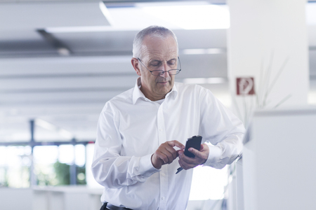 Businessman in open space office using smartphone LANG_EVOIMAGES