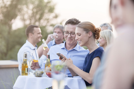Two colleagues looking at cell phone on a company party LANG_EVOIMAGES