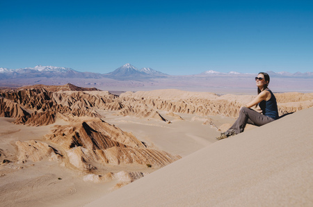 clime: Chile, Atacama Desert, woman sitting on a dune looking at view