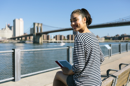 USA, New York City, portrait of smiling young woman with digital tablet sitting on backrest of a bench