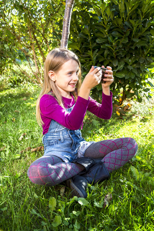 dungarees: Little girl sitting on a meadow in the garden taking a selfie with smartphone