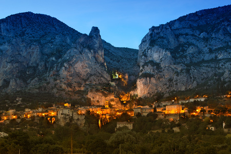 lighted: France, Alpes-de-Haute-Provence, View to village Moustiers-Sainte-Marie in the evening