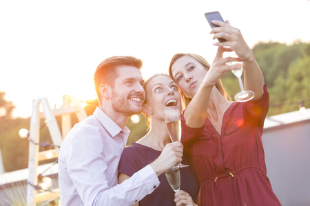 Happy colleagues taking a selfie on a company party