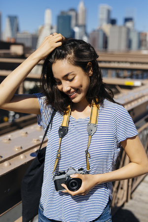 USA, New York City, portrait of smiling young woman with camera