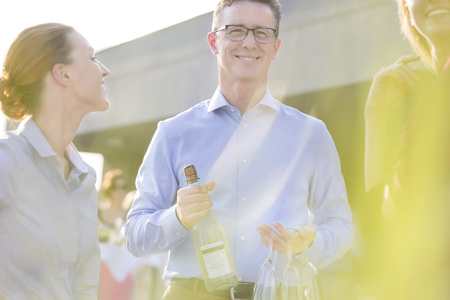 Smiling businessman with champagne bottle and glasses on a company party