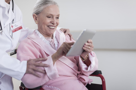 Smiling elderly patient in wheelchair using digital tablet LANG_EVOIMAGES