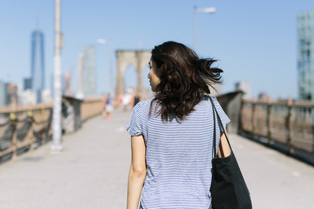 USA, New York City, back view of young woman walking on Brooklyn Bridge LANG_EVOIMAGES