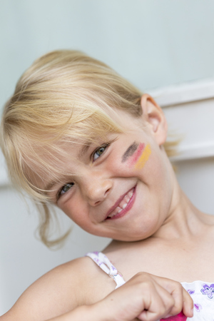 national identity: Portrait of blond little girl with German Flag painted on her cheek