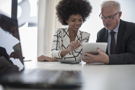 figuring: Businessman and woman with digital tablet and calculator