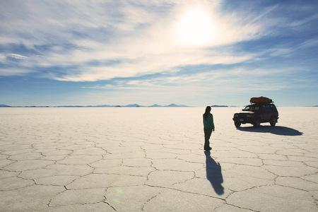 lighted: Bolivia, Potosi, Woman walking towards her 4x4 in Uyuni salt flats
